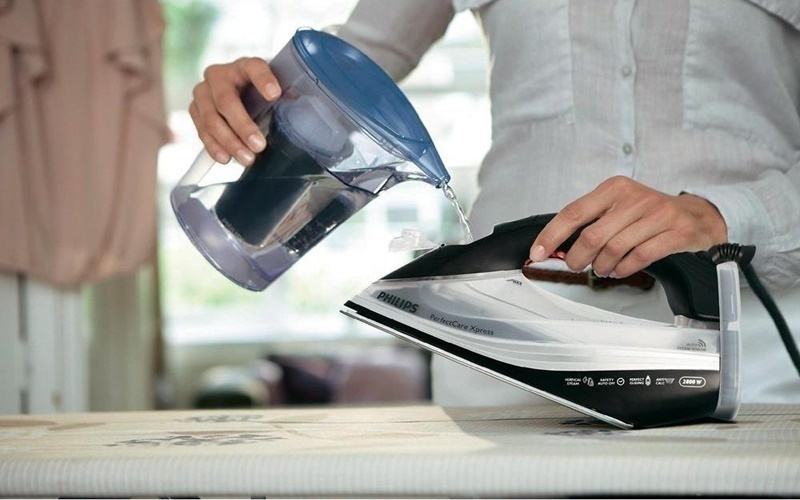 Châm nước vào bình bàn ủi mỗi khi hết nước