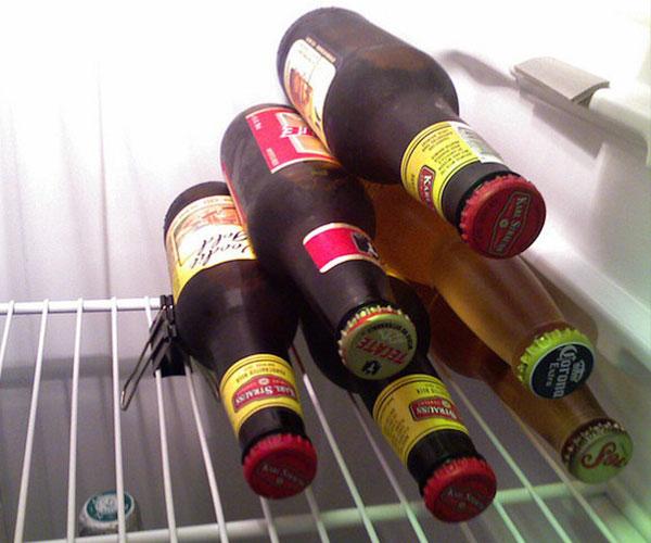 Chai nước đặt nằm ngang tiết kiệm diện tích thật đấy, nhưng chúng có thể lăng lông lốc trong tủ lạnh. Do đó, bạn cần dùng một chiếc kẹp bước ghim ở thanh chắn kim loại để giữ hàng chai nằm im đúng vị trí.