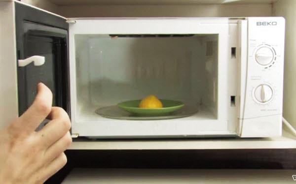 Bạn cắt nửa trái chanh đặt úp mặt xuống đĩa (như hình) rồi đổ thêm một muỗng nước, cho lò quay khoảng 1 phút. Khi chanh nóng lên và xuất hiện hơi nước trong lò, bạn dùng khăn lau sạch bên trong và rửa đĩa xoay.