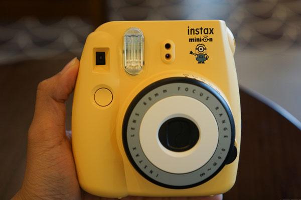 """Thiết kế của chiếc máy ảnh Fujifilm Instax Mini 8 Minion vẫn khá giống phiên bản gốc Mini 8 phiên bản gốc nhưng được logo Instax được """"điểm xuyết"""" thêm một chú Minion tạo nét đặc trưng cho thiết bị."""