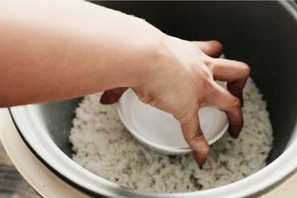 Đặt một bát nước lạnh vào giữa nồi cơm điện và ấn lực vừa phải xuống.