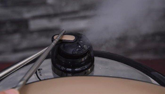 Đẩy nhẹ van xả áp bằng chiếc đũa để khắc phục tình trạng khó mở nắp nồi áp suất