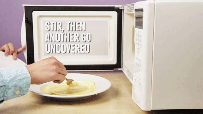 Sau đó, bạn mở lò và lấy dĩa trứng ra. Tuy nhiên, chưa thể ăn được đâu nhé! Bạn cần khuấy mặt trứng dàn phẳng tiếp rồi quay thêm 60 giây nữa.