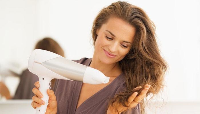 Sấy tóc trong tư thế thoải mái và ngồi trước gương sẽ giúp thời gian tóc khô nhanh hơn