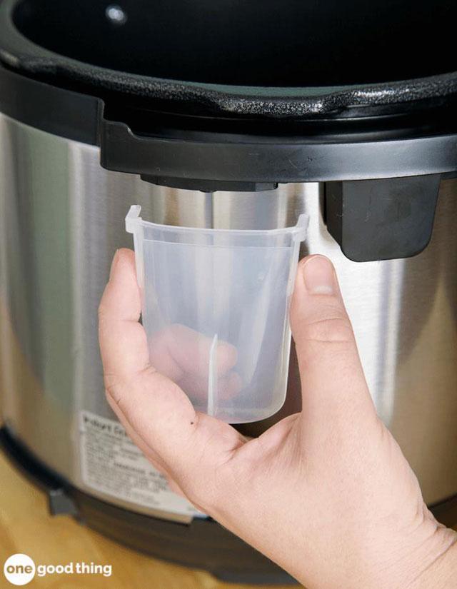 Rửa sạch cốc nước hứng bên ngoài nồi áp suất điện