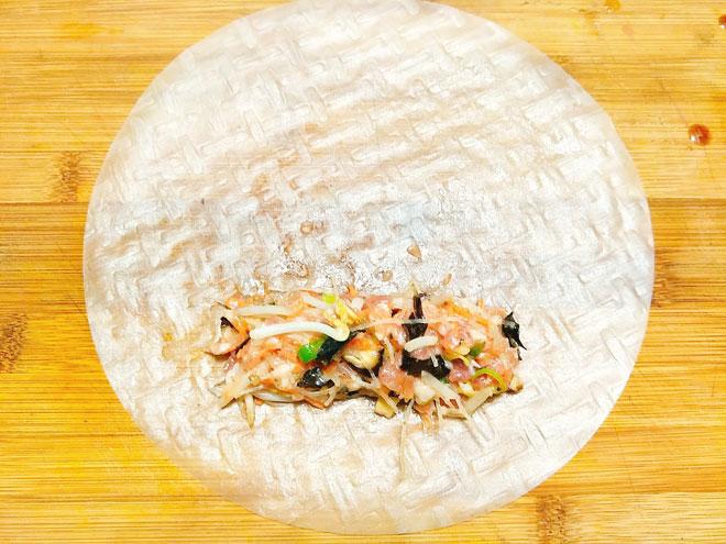 Bước 4: Gói nem, bạn nhúng vỏ đa nem vào nước cho mềm sau đó đặt trên thớt, múc 1 thìa nhân thịt đặt vào vỏ đa nem sau đó dàn thành hình cái đa nem cho dễ gói. Gập 2 mép bánh lại và cuộn kín, để khi rán nem không bị bục bạn không nên gói chặt tay. Cứ như vậy bạn tiếp tục gói cho hết nguyên liệu còn lại