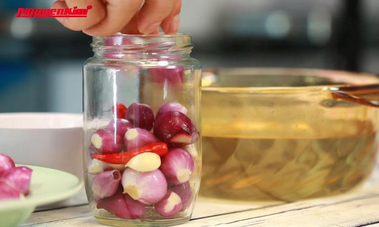 Gần xong rồi! Bạn hãy để nước ngâm hành nguội ở mức âm ấm. Tráng lọ thủy tinh qua nước sôi rồi cho hành, một ít ớt trái vào.