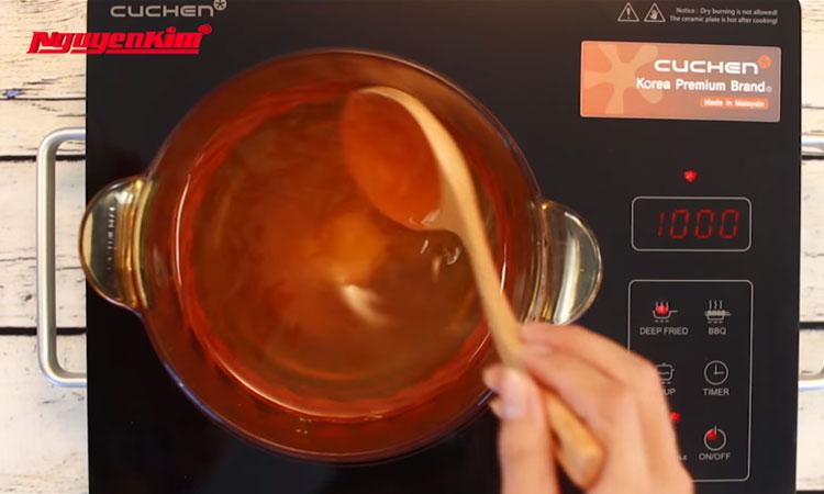 Bạn cho 1/2 lít nước lọc, 0.2 lít nước mắm ngon, 500 gram đường, 1 muỗng cà phê muối vào nồi, khuấy đều, đun sôi trên bếp điện.