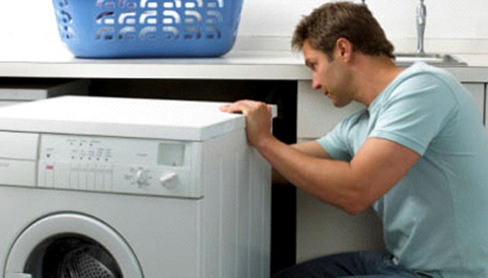 mở tấm lưng máy giặt để kiểm tra dây đai
