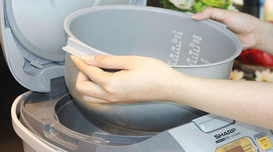 Nên dùng cả 2 tay để tránh nồi đặt xuống không đều dễ gây tổn hại rơ le nhiệt
