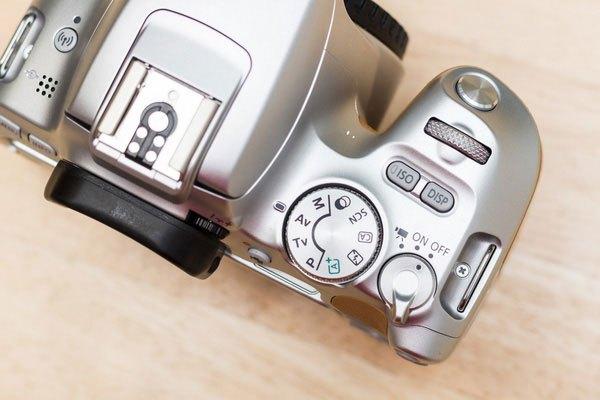 Đỉnh máy ảnh 200D có chân cắm flash rời, vòng xoay chỉnh chế độ, nút bật/ tắt máy, nút chỉnh iso và nút bật/ tắt màn hình.