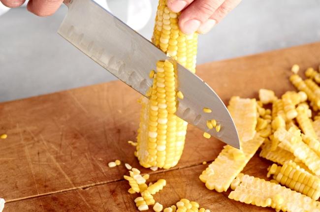Dùng dao cắt theo chiều dọc của trái ngô để tách lấy hạt ngô