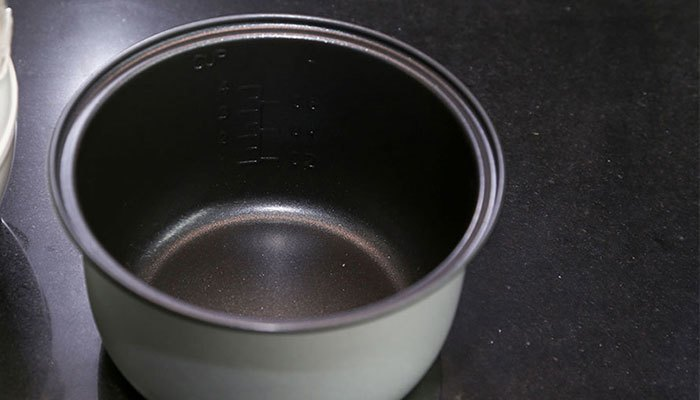 Lồng nồi cơm điện bị bong tróc làm cơm dính lại gây khét